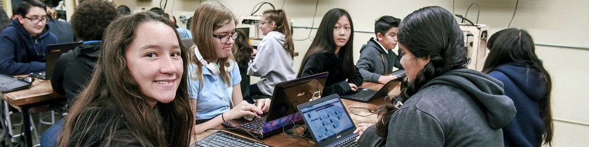Several Fresno Unified students sitting at a table with laptops