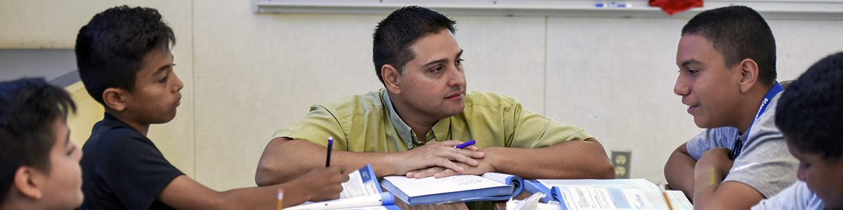 A teacher crouches at a table with students