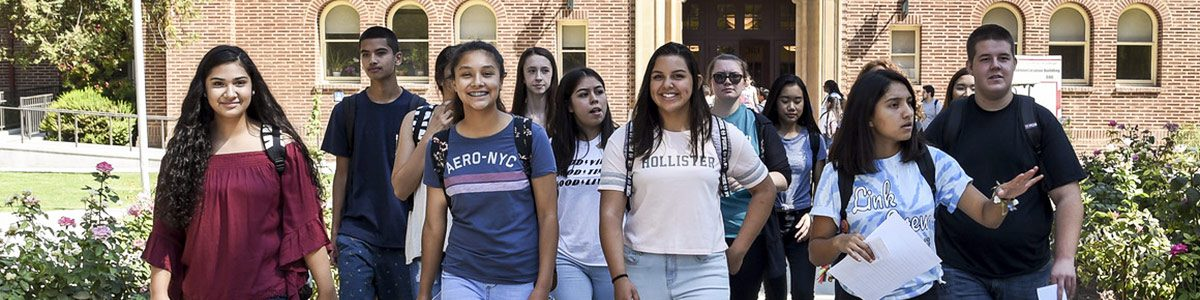 A group of several Fresno Unified students walking towards the camera with a building in the background