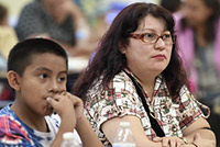 A mother and child sitting at a Fresno Unified event